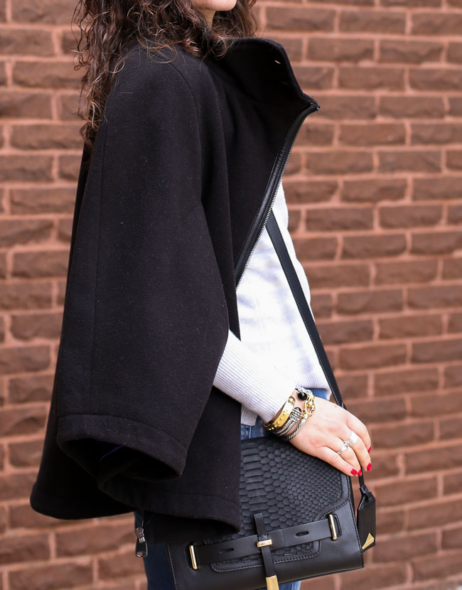 casual outfit with a black cape worn over a striped sweater, boyfriend jeans and gray heels