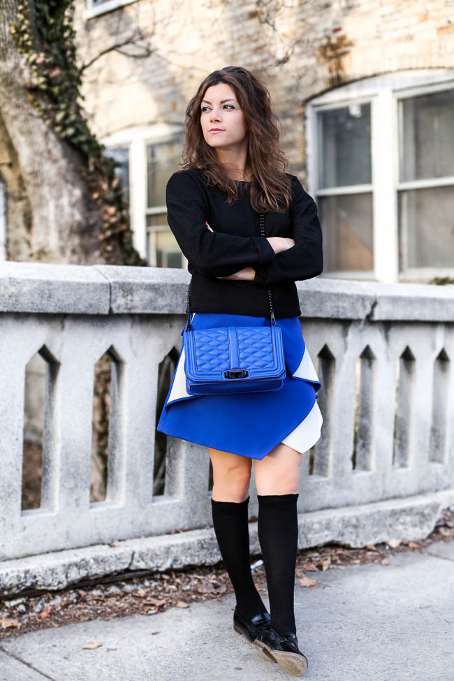Pleated cobalt skirt with a black crop top, knee high socks and loafers