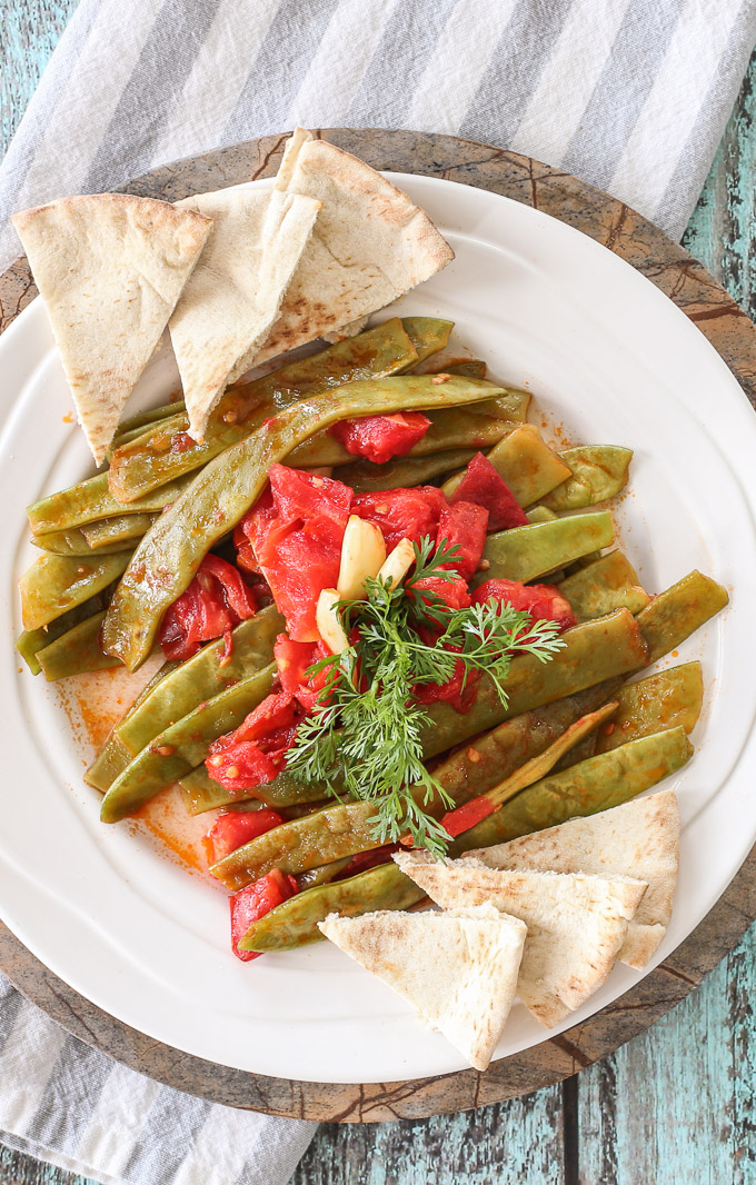 Syrian cooking: vegan side dish with sautéed garlic tomato green beans topped with cilantro