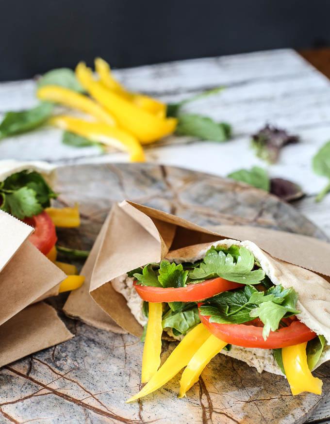 Pepper, tomato, lettuce and eggplant dip stuffed vegetarian pita sandwiches.