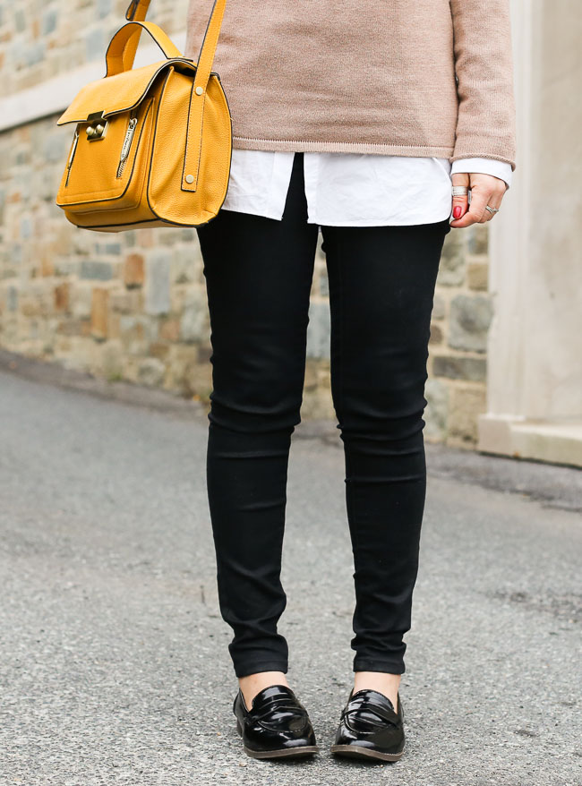 a casual fall outfit with a beige turtleneck, yellow bag, black denim and loafers